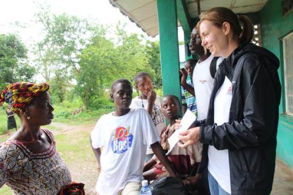 Ella toont aan de moeder van een ebola-patiënt het bewijs waarop staat dat haar zoon volledig genezen is. © P.K. Lee / AZG