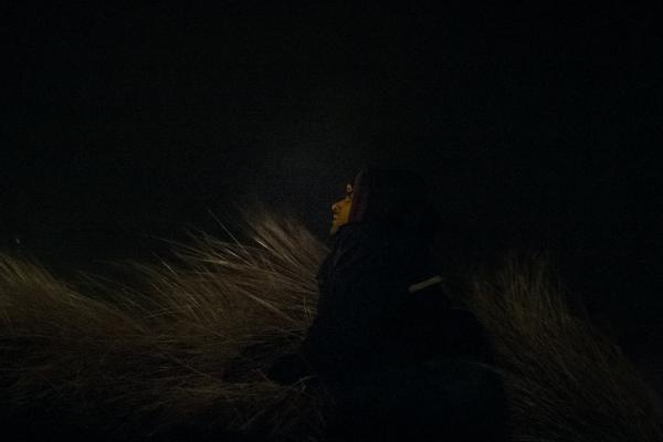 1er février 2016 – Shahin (27 ans), originaire d'Iran, a le regard perdu au loin, bien au-delà des dunes. Une fois le combi de police passé, il tente sa chance. © Ans Brys